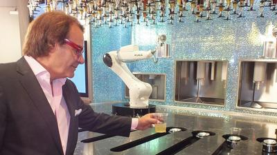 Owner Rino Armeni collects a cocktail freshly blended by one of the two robotic bartenders deployed at Tipsy Robot. Armeni expects the entertainment factor to be a big draw. (Jay Jones / For The Times)